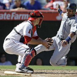 Seattle Mariners' Franklin Gutierrez is tagged out at home by Los Angeles Angels catcher Chris Iannetta in the fifth inning of a baseball game in Anaheim, Calif., Thursday, Sept. 27, 2012. Gutierrez tried to score from first on a double by Kyle Seager