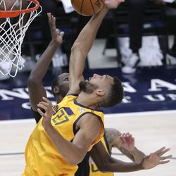 Utah Jazz center Rudy Gobert (27) and San Antonio Spurs center Gorgui Dieng (7) reach for the ball during an NBA game at Vivint Smart Home Arena in Salt Lake City on Monday, May 3, 2021. The Jazz won 110-99.