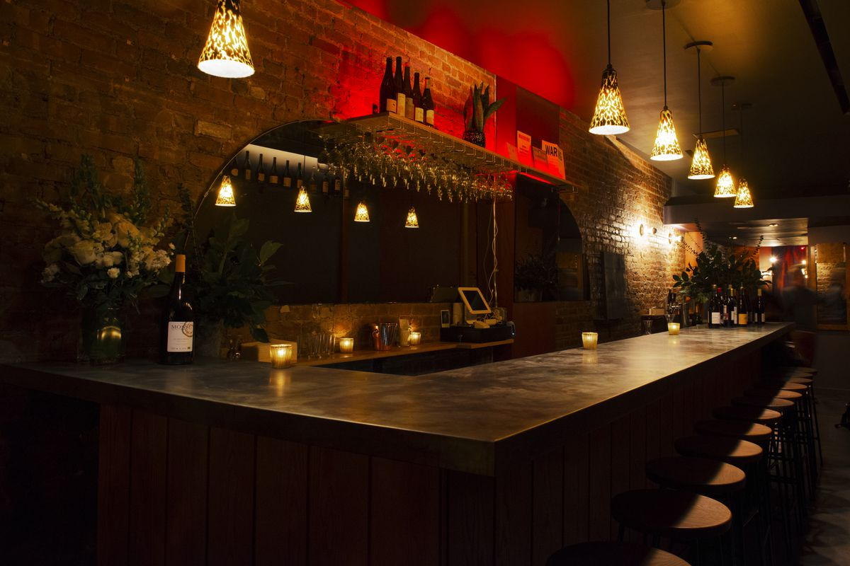 A dark bar with cone-shaped lights hanging above and a reddish glow in the back.