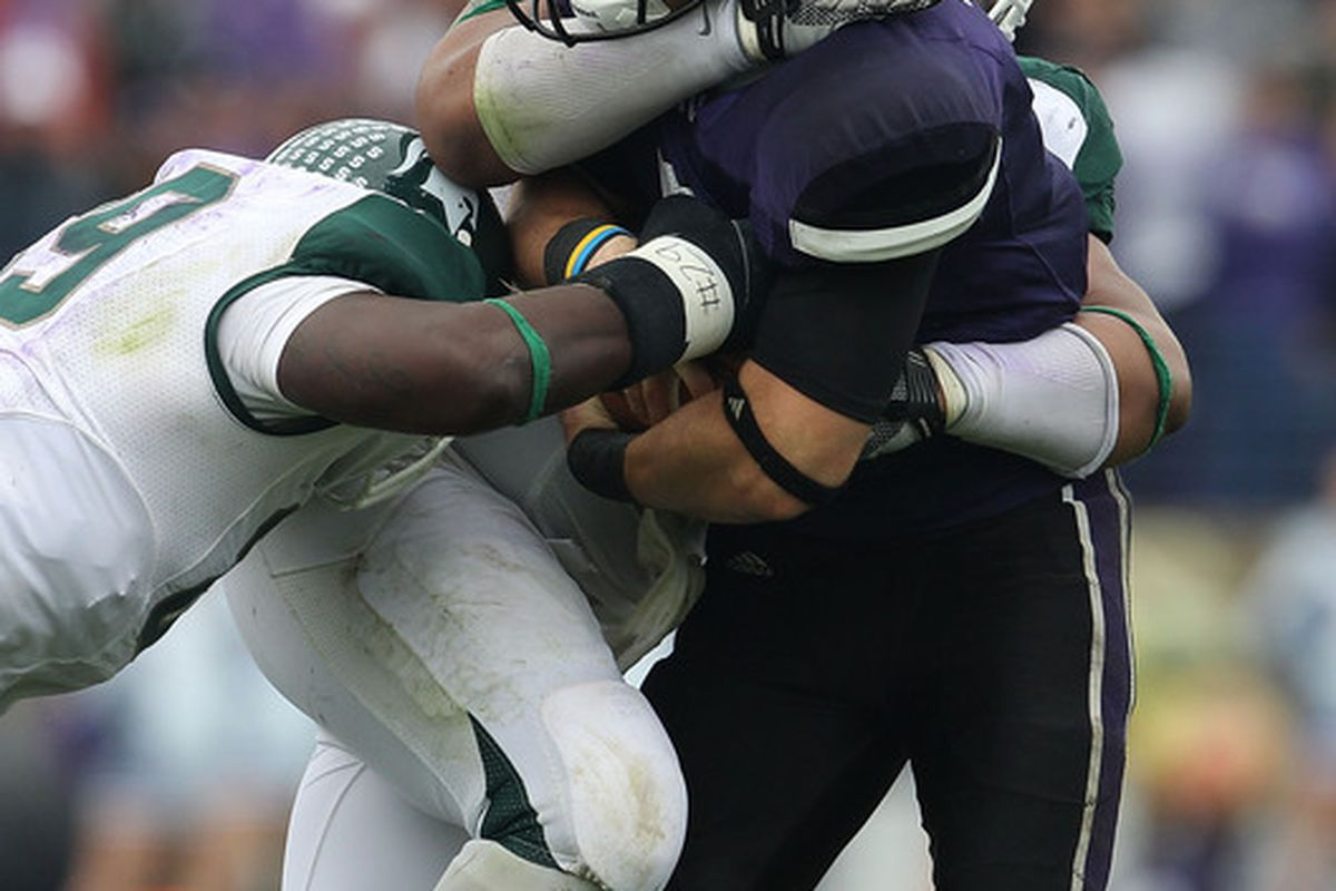 The sweet embrace of the strangle-tackle.   Don't fight it, Persa. (Photo by Jonathan Daniel/Getty Images) *** Local Caption *** Dan Persa; Colin Neely; Jerel Worthy