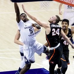 Brigham Young Cougars forward Gideon George (5) goes to the hoop against Pacific Tigers guard Broc Finstuen (24) at the Marriott Center in Provo on Saturday, Jan. 30, 2021.
