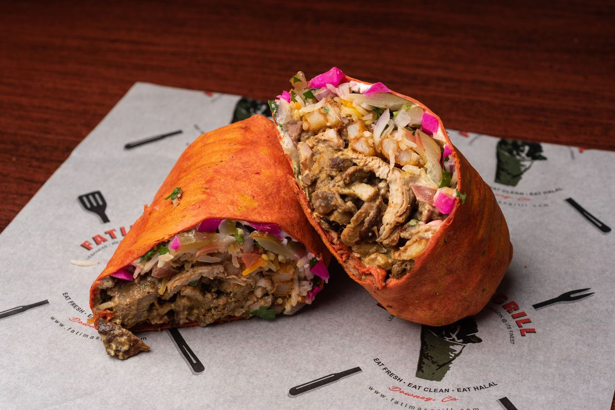 A large shawarma sandwich wrap on a sheet of paper.
