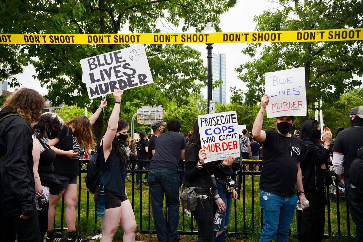 "People in black holding signs reading ""Blue Lives Murder"" and ""Prosecute cops who committed murder"" standing under yellow faux police tape printed with the words ""DON'T SHOOT."""