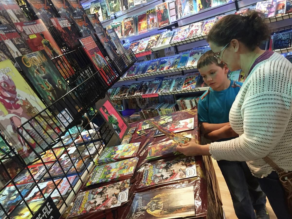Jennifer Broschinsky and her son, Ian, peruse comic books at Night Flight Comics in Murray during Free Comic Book Day, Saturday, May 7, 2016.