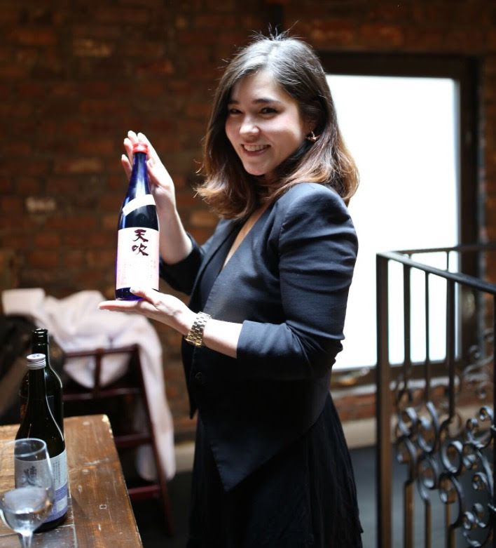 Jessica Joly smiles and holds a bottle of sake.