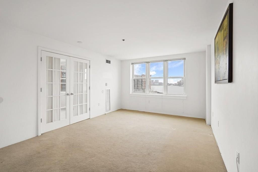 An empty bedroom with a set of windows and a set of closed glass doors.