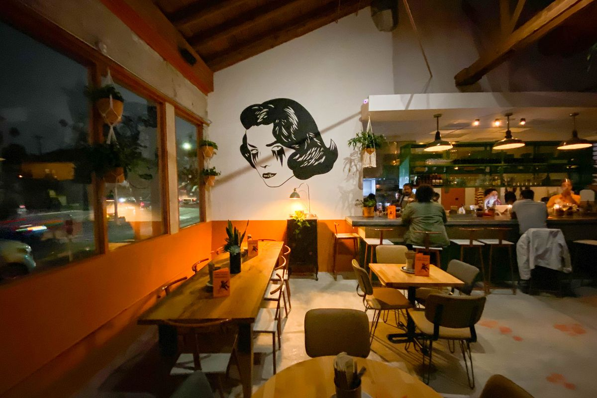A dinnertime restaurant with mood lighting highlights a mural of a crying woman.