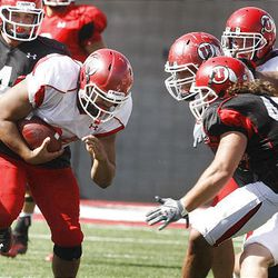 Tauni Vakapuna, in white jersey at left, lowers his head before colliding with Boo Andersen in Tuesday's Ute scrimmage.