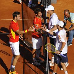 Mike Bryan of US, bottom right, and his fellow teammate, Bob Bryan, top right, are congratulated by Spain's Marcel Granollers, left, and Marc Lopez, at the end of the doubles and third match of the Davis Cup World Group semifinal tennis match in Gijon, northern Spain, Saturday, Sept. 15, 2012. US Davis Cup double team won 3-6, 6-3, 5-7, 5-7.