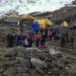 In this photo provided by Nepalese airline Simrik Air, rescuers attend to injured victims, unseen, after an avalanche at the base camp of Mount Manaslu in northern Nepal, Sunday, Sept. 23, 2012. The avalanche swept away climbers on a Himalayan peak in Nepal on Sunday, leaving at least nine dead and six others missing, officials said.
