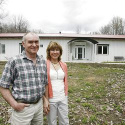 Eddy Rall and Patty Momenee stand in front of the home they designed and built in the woods outside Rising Sun, Ohio.
