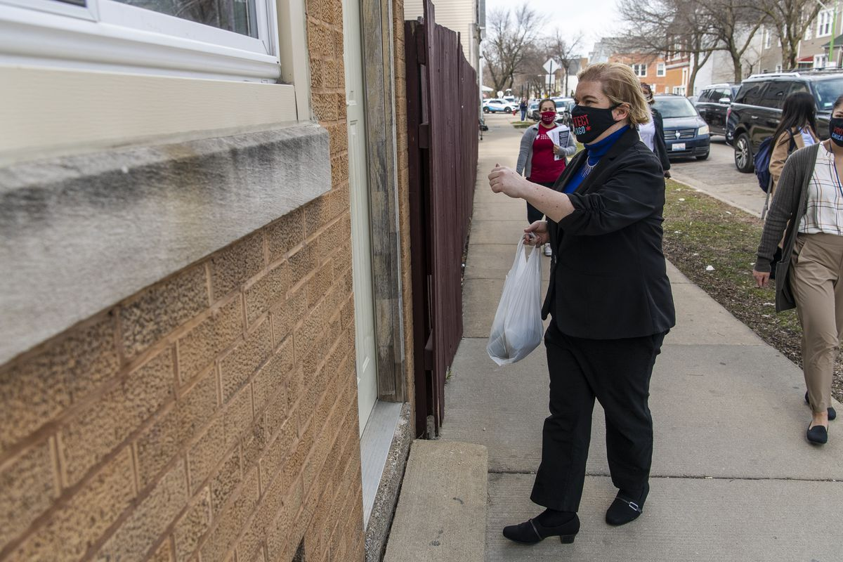 Dr. Allison Arwady knocks on a door of a home in March in the Back of the Yards neighborhood to give the resident a mask and information about getting a COVID-19 vaccine.
