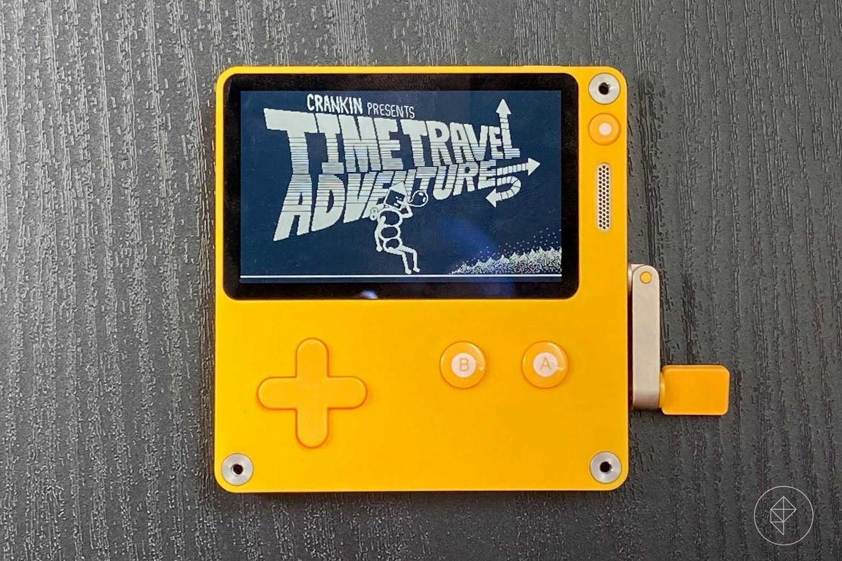 A Playdate sits on a black wooden surface. On the screen are the words Time Travel Adventures and a robot scratching his head.