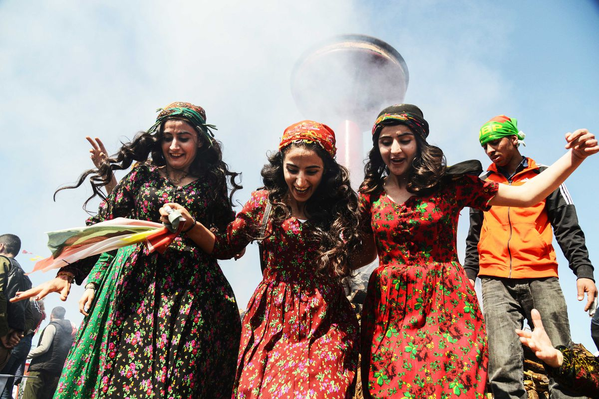 Women in traditional Kurdish outfits smile in front of a bonfire.
