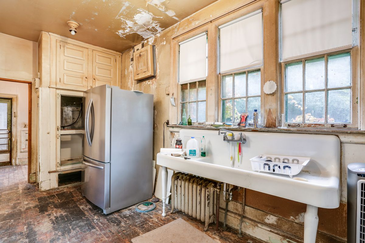 The kitchen has a silver refrigerator and wide white sink. The floors have been removed and the paint is cracking on the ceiling.