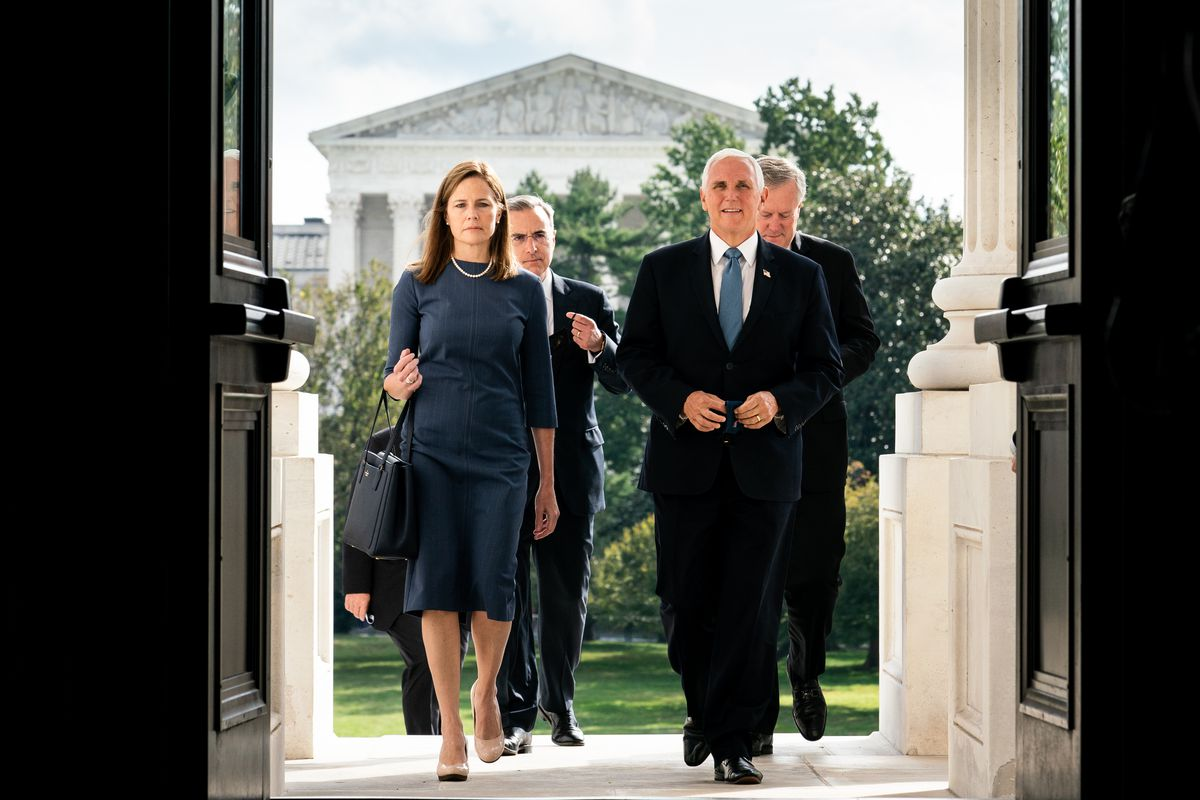 Amy Coney Barrett and Vice President Mike Pence walk into the US Capitol building.
