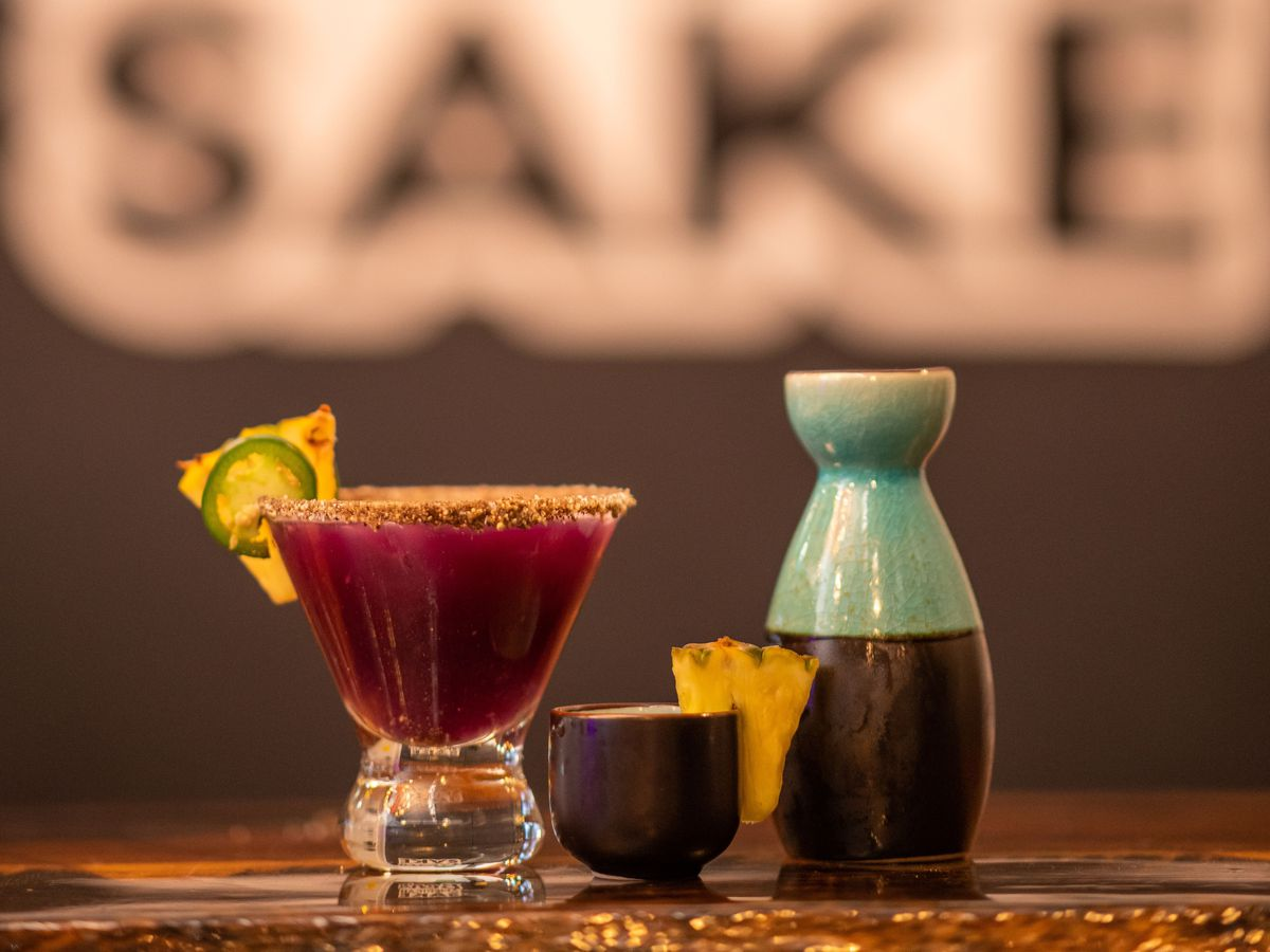 A colorful carafe, a cocktail with a bright purple drink, and a small sake cup garnished with a pineapple wedge, on a wooden counter