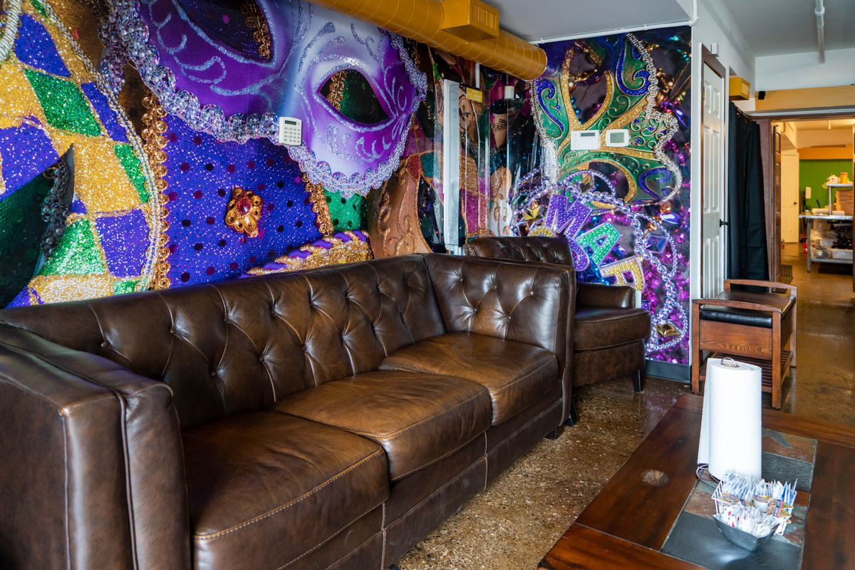 A leather couch inside Dat Creole Soul, with a colorful Mardi Gras-themed mural behind it