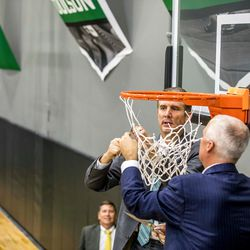 NUVI Chairman and CEO Keith Nellesen (front) and Utah Valley University President Matthew S. Holland cut down the nets to officially open the NUVI Basketball Center on the campus of Utah Valley University in Orem, Utah.
