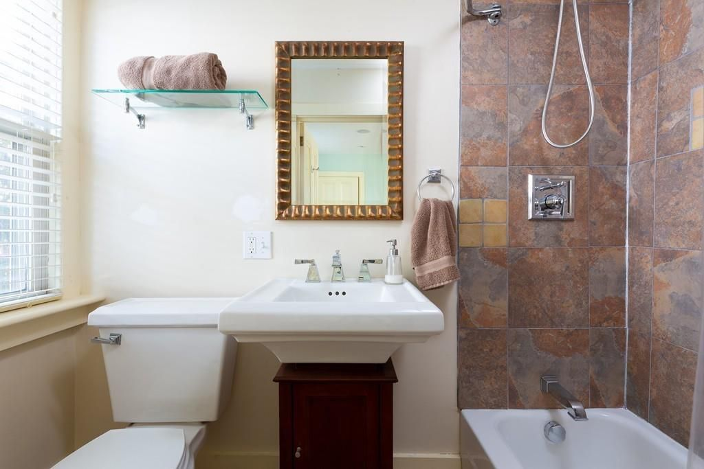 A modern bathroom facing the sink and toilet, and there's a shower next to them.
