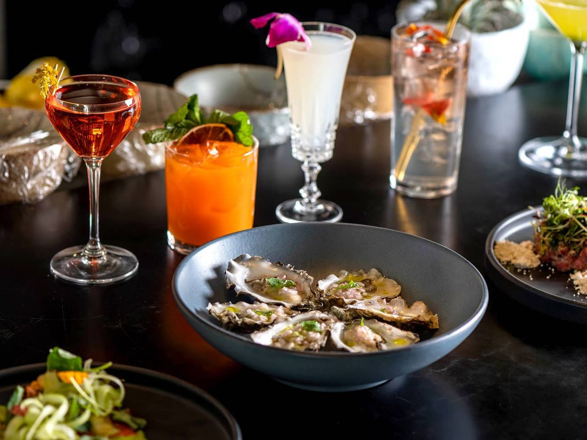 A plate of oysters next to several colorful cocktails on the bar at Inland Pacific Kitchen