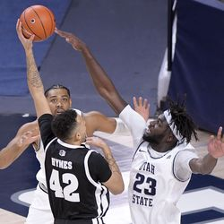 Nevada forward Kwame Hymes (42) has his shot blocked by Utah State center Neemias Queta (23) as forward Alphonso Anderson helps defend during the first half of an NCAA college basketball game Sunday, Feb. 28, 2021, in Logan, Utah.