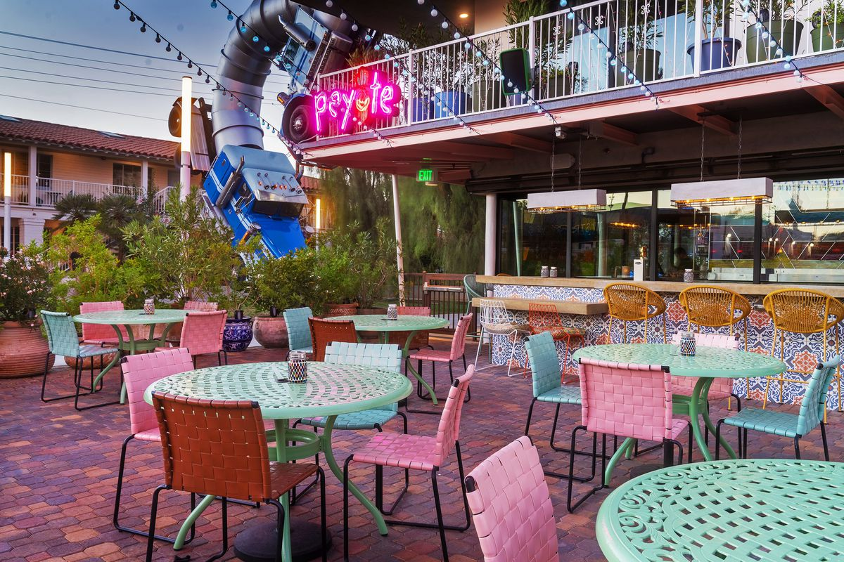 A patio with pink chairs and light mint green tables.