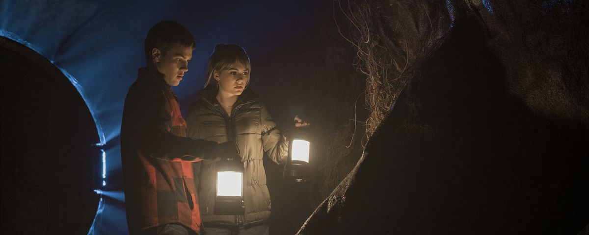 Teenager siblings Kinsey and Tyler shine square, glowing lanterns on a big, black cave rock, while the blue outline of an eerie, omega-shaped door glows behind them.