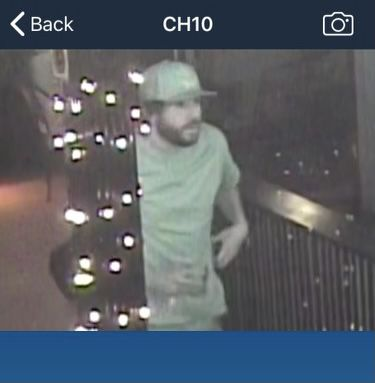 a screencap of a white man in a baseball hat and a t-shirt exiting a bar