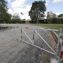 """A gate is shown outside the former Eagle Elementary School in West Bloomfield, Mich., Wednesday, Aug. 29, 2012. This affluent Detroit suburb with a diverse mix of religions and races and center of the region's Jewish community is the latest battleground over mosque construction, as some residents push back against a school district's decision to sell a vacant elementary school to an Islamic group. The Farmington Hills school district defends its agreement to sell Eagle Elementary School to a Muslim association and an administrator says opposition now can be classified as """"Islamophobia."""""""