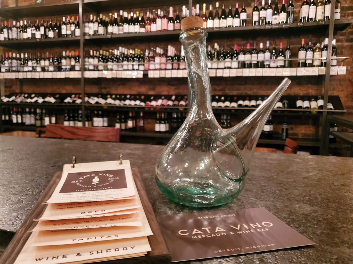 A glass porron with a cork stopper sits on the counter at Cata Vino with menus in the foreground and wine bottles in the background.