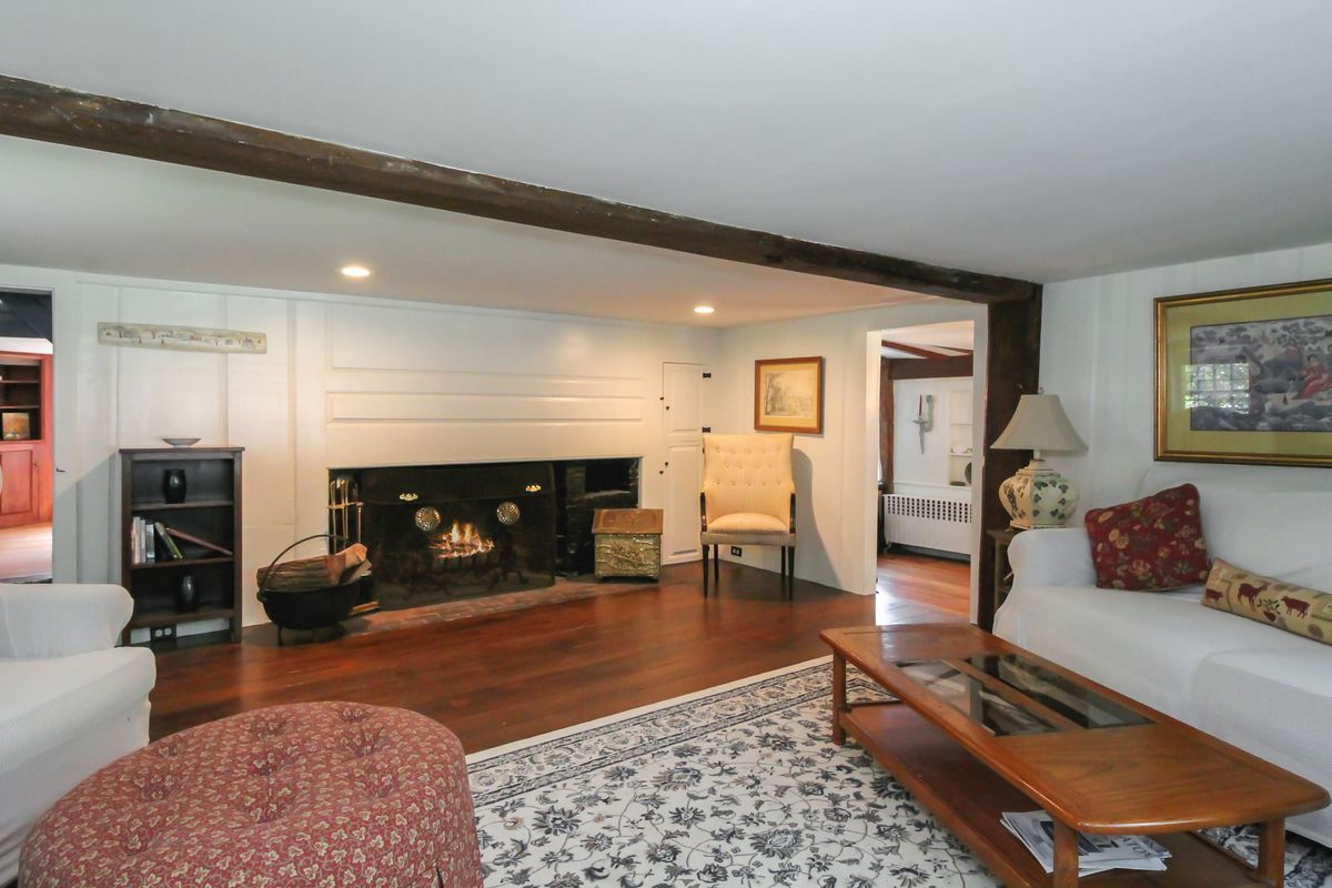 A living room features an exposed beam, fireplace, white walls, pine floors, a coffee table, and various couches and armchairs.