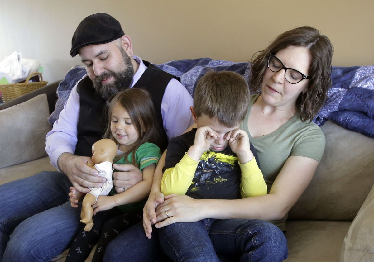 Jake Martinez, who has epilepsy, holds his daughter Jenny, while his wife Kat, holds their son Joe, at their home in Murray, Utah. Martinez said Obamacare made it possible to get affordable coverage for himself, his wife and their children. Without it, he