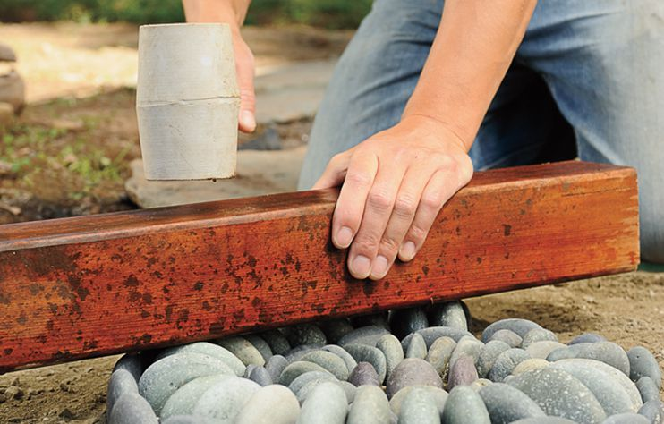 Person Places Lumber Across Pebble Mosaic To Level It
