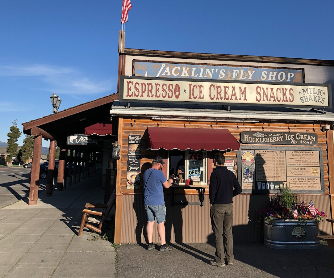 A wooden cabin with a walk-up window selling coffee, ice cream, pastries, and other snacks. A small crowd of three is gathered outside, and the shop is backdropped by a bright blue sky.