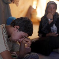 In this Tuesday, Sept. 11, 2012 photo, Basel Baradan, an 18-year-old farmer who fled his southern restive border town of Daraa, Syria with his family in July, wipes his eyes as he speaks during an interview at the Zaatari Refugee Camp, in Mafraq, Jordan. Jordan now hosts 200,000 Syrians, the largest number of refugees of any neighboring country. After months of delay, Jordan finally opened its first official refugee camp in July at Zaatari, near the border with Syria.