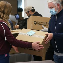 Erin Nolte, of Yarrow Hospice, accepts a donation of much needed N95 masks from Chris Ahern, Zagg CEO, at the company's headquarters in Midvale on Tuesday, April 14, 2020.The company is donating 10,000 of the masks to hospitals, medical professionals and high-risk individuals to help combat the spread of COVID-19 in the communities in which the company operates.
