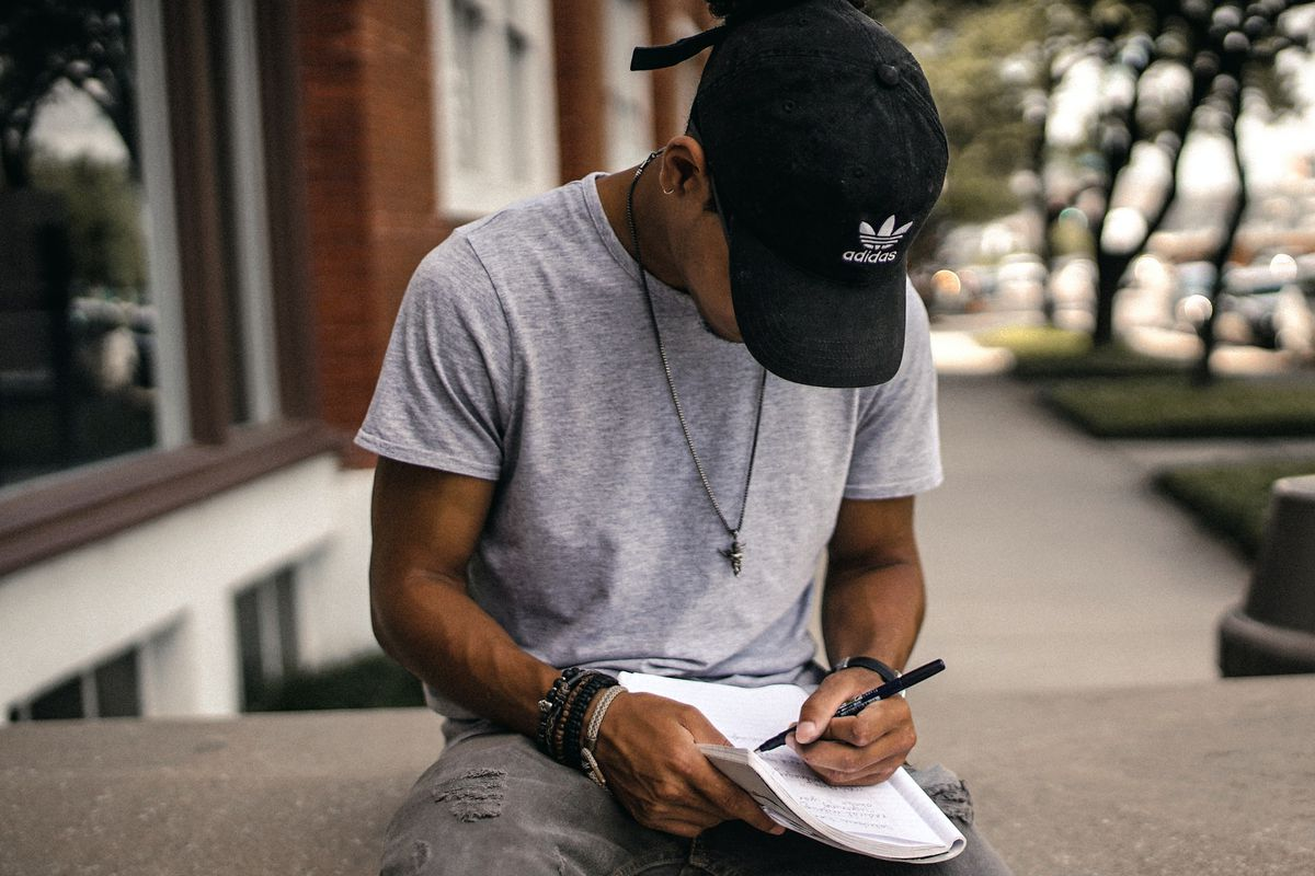 Student wearing a baseball cap sitting outside writing in a notebook.