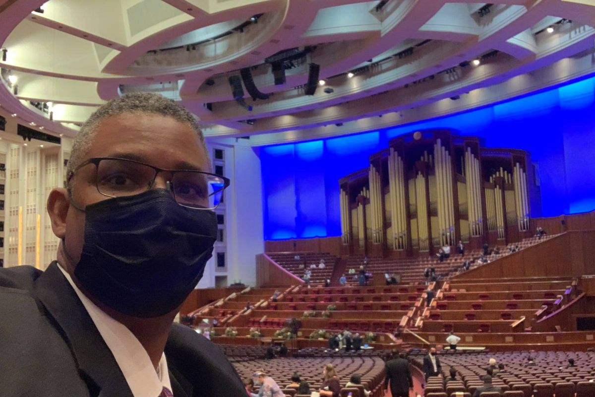 Thom Reed wears a face mask during a rehearsal for a multicultural choir in the Conference Center in Salt Lake City.