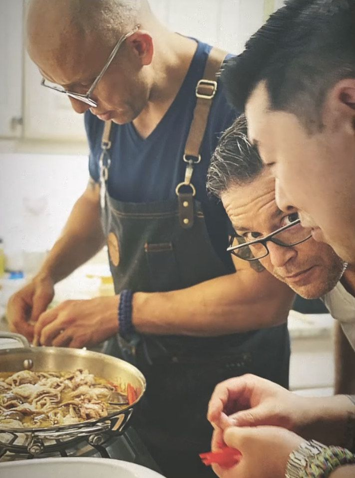 Ronaldo Linares, Christopher Daugherty, and Young Cho (left to right) hovering over a counter while preparing food.