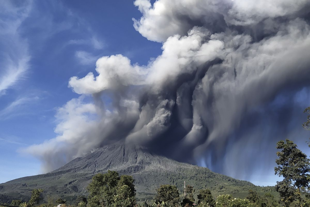 """Mount Sinabung spews volcanic materials during an eruption, in Karo, North Sumatra, Indonesia, Sunday, Aug. 23, 2020. Sinabung is among more than 120 active volcanoes in Indonesia, which is prone to seismic upheaval due to its location on the Pacific """"Ring of Fire,"""" an arc of volcanoes and fault lines encircling the Pacific Basin."""