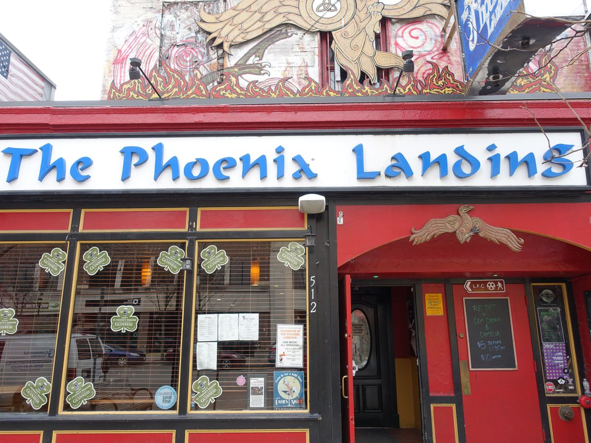 bright red exterior of a bar with a long white sign that says The Phoenix Landing in blue font