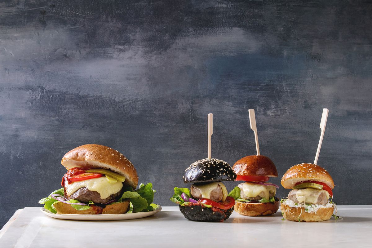 Variety of homemade classic and mini burgers in wheat and black buns with beef and veal cutlets, melted cheese and vegetables on white marble table.