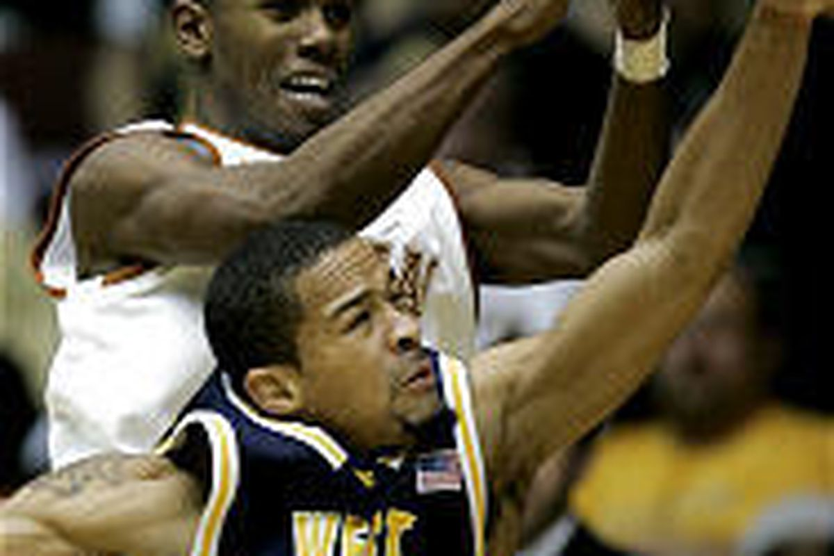 West Virginia guard J.D. Collins (1) breaks up a pass intended for Texas guard Daniel Gibson in the Guardians Classic on Monday.