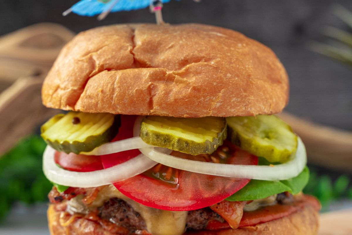 a burger with onions, pickles and tomatoes and topped with a blue cocktail umbrella