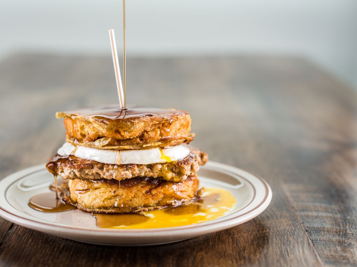 Biscuit sandwich with a sausage patty, a fried egg, apple butter, and maple syrup