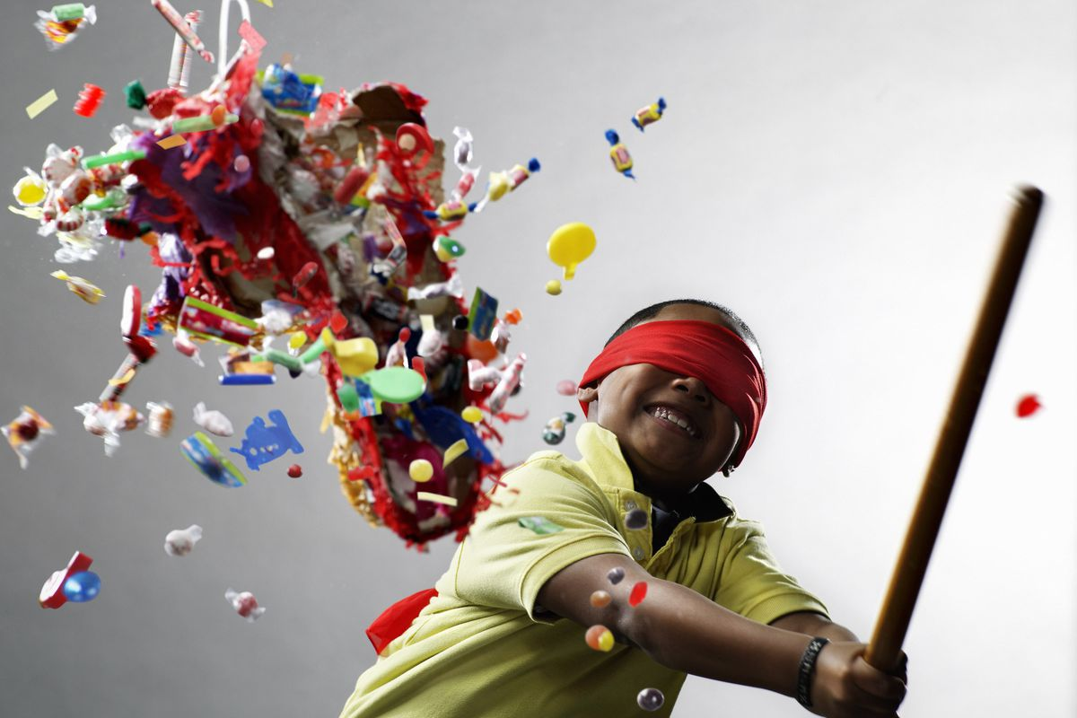 A photo of a boy smashing a piñata with candy flying out