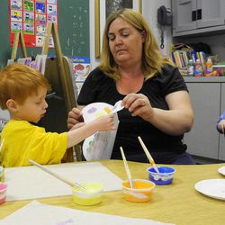 In this April 19, 2012, photo, teacher Julie Singleton helps her 4-year-old students paint butterflies at the Sunshine School in Marietta, Ga. The school is among the first to sign up for a new statewide quality rating system.
