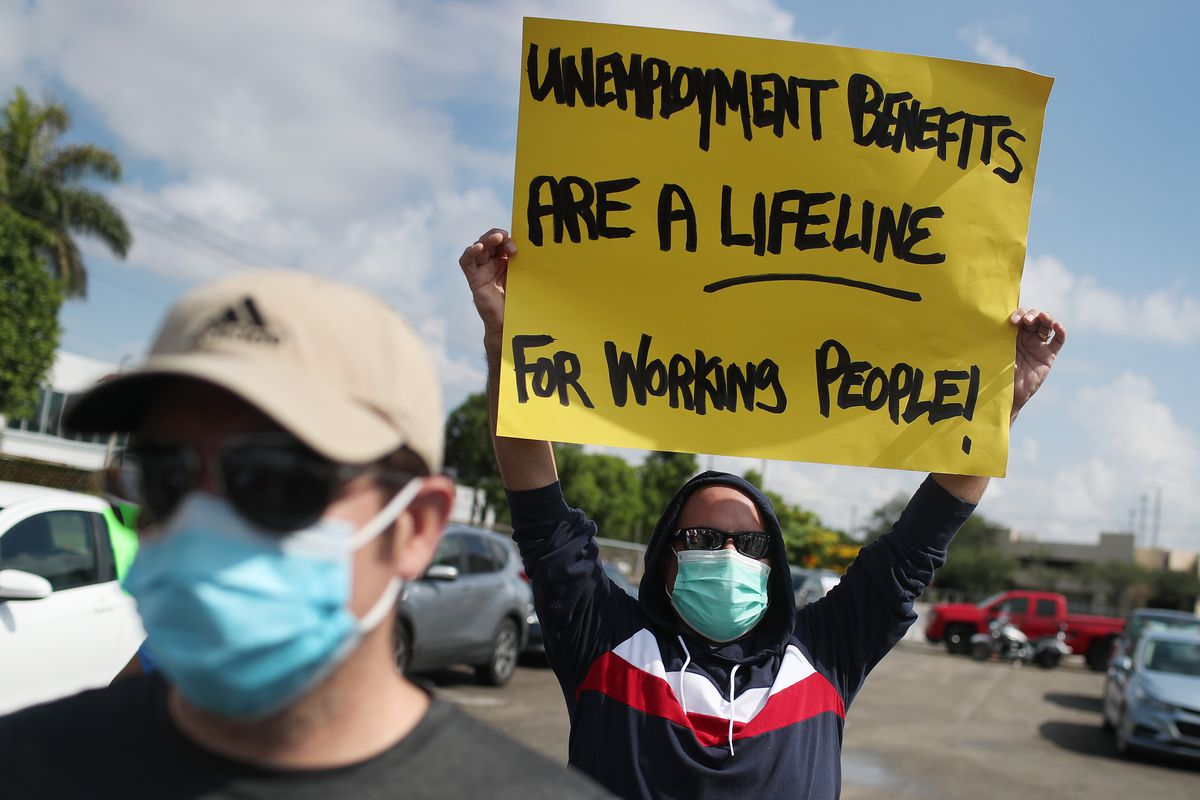"""A protester holds up a sign that reads, """"Unemployment benefits are a lifeline for working people!"""""""