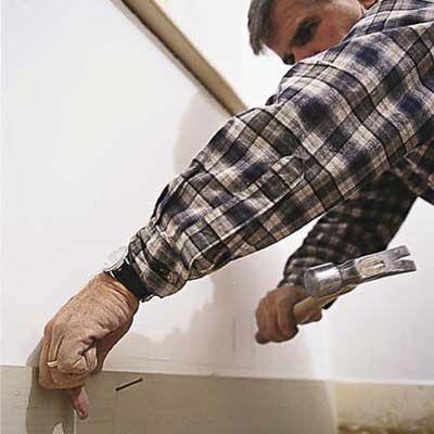 Man Nails Baseboard To Wall With Hammer And 8d Finish Nails